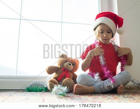 Little boy in red cap of Santa Claus celebrates Christmas