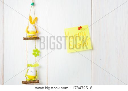 Egg Decoration Bunny On White Wooden Background And Happy Easter Text On The Yellow Sticker.