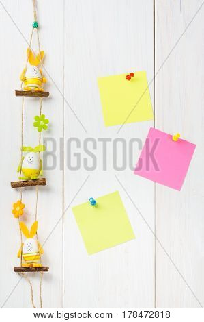 Egg Decoration Happy Easter Bunny On White Wooden Background With Yellow And Pink Sticker Notes.