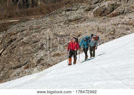 Group of Alpine Climbers with Backpacks and climbing Gear in protective windproof Clothing in bright Colors heavily walking on Snow Slope