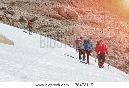 Group of Climbers with Backpacks and climbing Gear in protective windproof Clothing walking on Snow Slope Nepalese Porter using traditional Head Strap with Basket shining Sun.