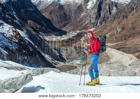 One Young Mountain Climber in red Jacket and high Altitude Boots staying on Glacier using Cell Phone in extreme Conditions Rocks and Valley on Background