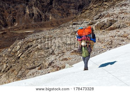 Nepalese Porter carrying traditional handmade Basket with luggage of mountain expedition using head strap on snowy glacier