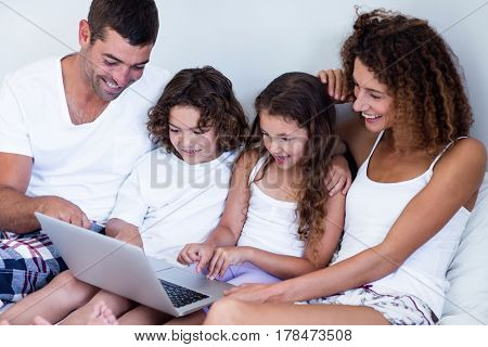 Family using laptop together on bed in bedroom