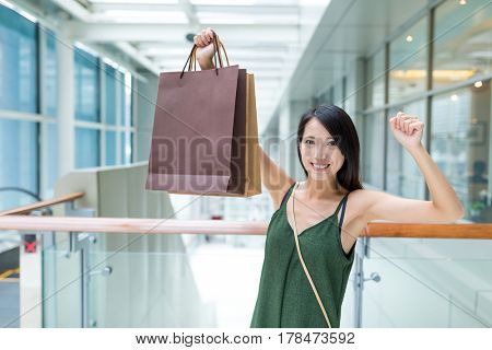 Excited woman holding up shopping bag