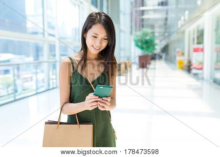 Woman using cellphone in shopping mall