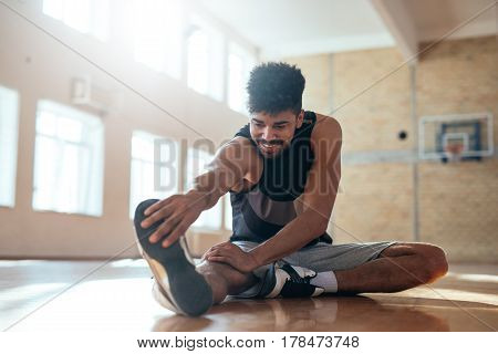 Photo of an african american basketball player doing some stretching exercises before practice.