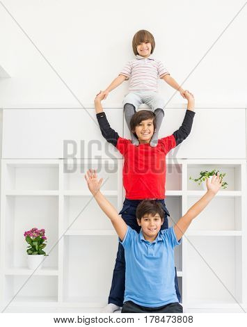 Cheerful funny children having fun and posing line up piggyback in new modern home