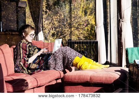 Adult Lady in travel Style colorful Clothing Poncho and yellow socks sitting on red Sofa and working on portable Computer in Hotel Lobby interior with Forest outside windows.