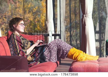 Adult Lady in travel Style colorful Clothing Poncho and yellow socks sitting on red Sofa and working on Computer in Hotel Lobby interior with Forest outside windows.