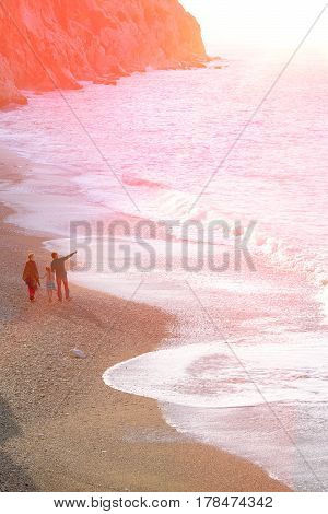 Family of three People Mother Father and baby Daughter walking together on Ocean Beach with beautiful Sea Surf soft Tone and shining Sun