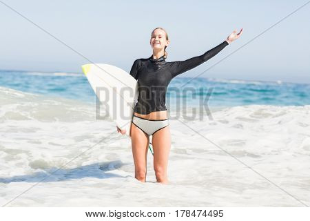 Woman with surfboard standing in sea with arm outstretched