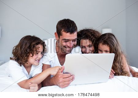 Happy family using laptop together on bed in bedroom