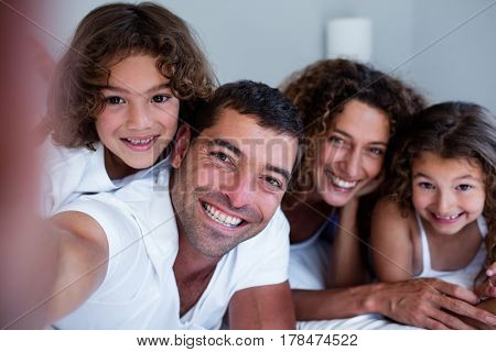 Portrait of happy family lying on bed at home