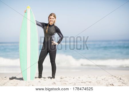 Woman in wetsuit holding a surfboard on the beach on a sunny day