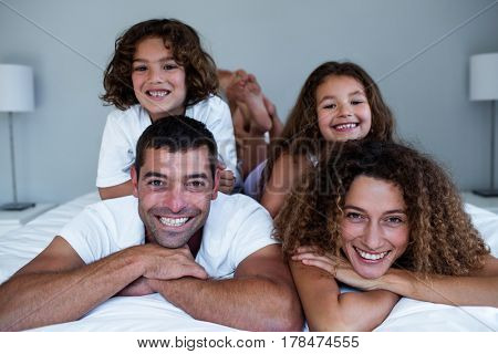 Portrait of family lying on top of each other at home