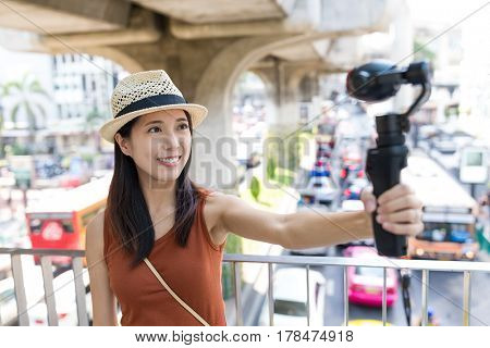 Woman taking selfie movie by video stabilizer