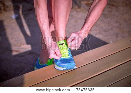Athlete during training tying shoelaces on sneakers summer.