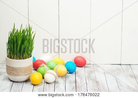 Colored easter eggs flower pot with green grass on the wooden background. Space for text. Selective focus.