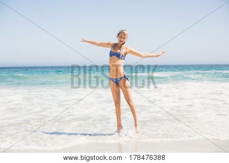 Carefree woman in bikini standing on the beach with arms outstretch