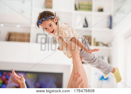 Child playing with father on house sofa flying airplane open hands