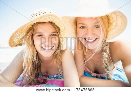 Portrait of happy women lying on the beach at sunny day