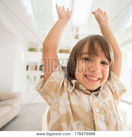 Happy child with hand up indoors