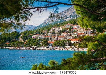 view of the Brela village through green pines Makarska Riviera Croatia