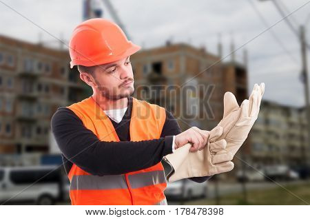 Builder Putting Protection Gloves On Hands