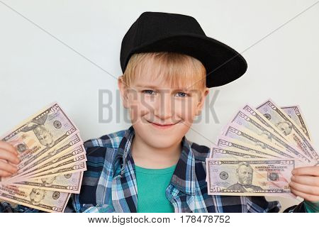 A portrait of delighted little stylish boy in black cap holding money in his hands. A happy child male holding cash isolated over white background. Kid holding currency notes.Boy is counting money