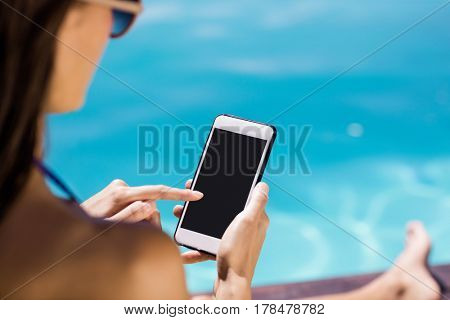 Over shoulder view of brunette using smartphone poolside