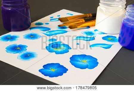 Three acrylic paint colors and flat brushes. Basic one stroke painting painting strokes explained for beginners. Hand drawn folk blue flowers creative work place on the black table