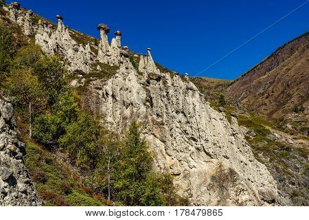 Scenic autumn view with high rocks in the form of stone mushrooms on a background of mountains and blue sky