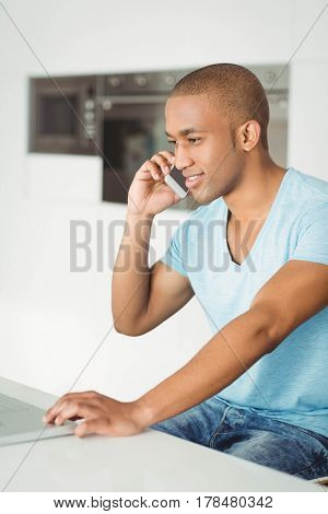 Smiling man calling and using laptop in the living room at home