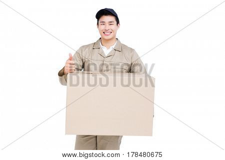 Delivery man with cardboard box giving a thumbs up on white background