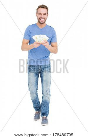 Young man counting currency notes on white background