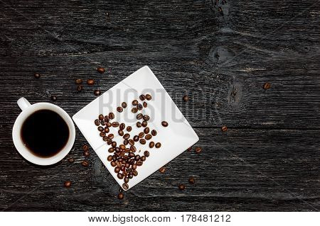 coffee cup and saucer with coffee beans on a black wooden background.