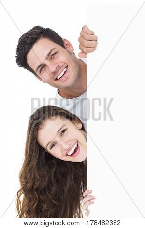 Happy couple looking over a poster on white background