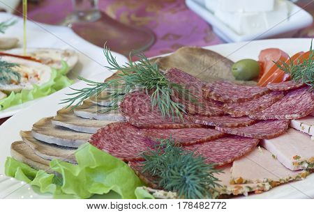 Different meat delicacies in a plate on a server table close-up