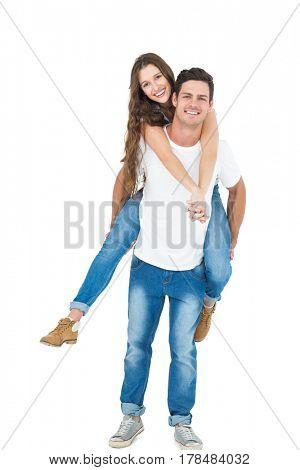 Boyfriend giving piggy back to girlfriend on white background