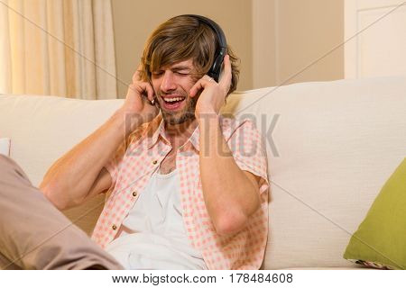 Handsome man listening to music with headphones sitting on the couch