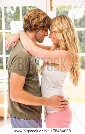 Cute couple hugging in front of the window