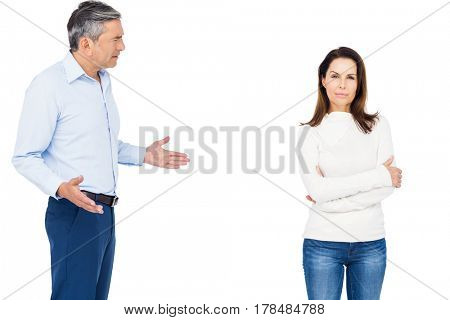 Couple arguing while standing against white background