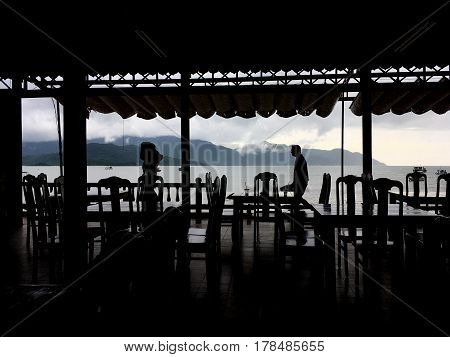 the view through the café to the sea, plenty of tables and chairs, subdued, the silhouettes, the roof in the form of a canopy above the café, the waiters at the background to see the sea, mountains with low clouds