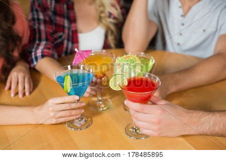 Friends toasting with cocktails at bar