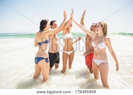 Happy friends giving a high five on the beach on a sunny day