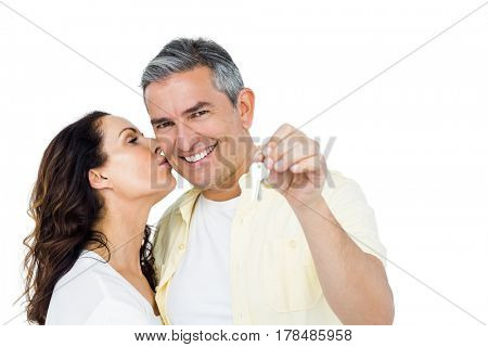 Portrait of happy couple holding home keys against white background