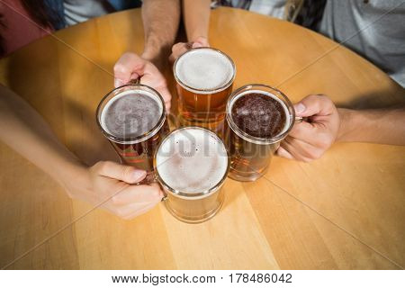 Friends toasting with beers at bar