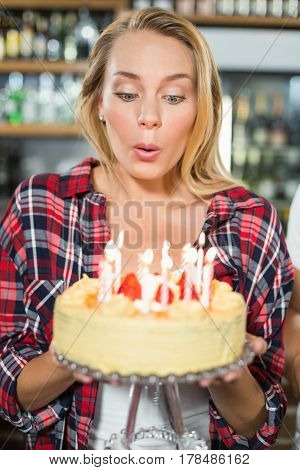 Woman blowing out candles on a cake