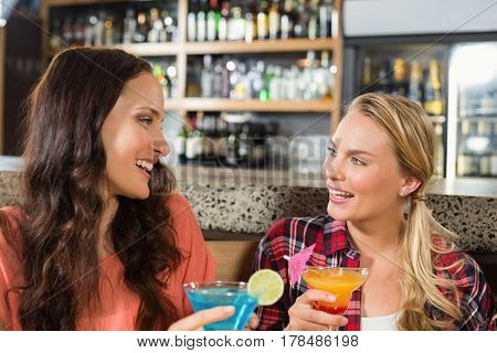 Women lookin at each other while holding glasses of cocktail